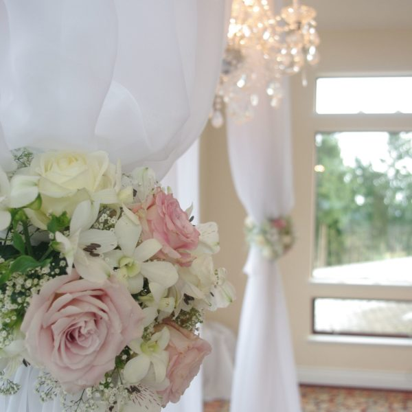 <p>This elegant ceremony archway was designed with white sheer fabric, crystal chandelier and beautiful flower accents.<br /> ©Christina Leaman</p>